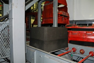Mold entering Hunter HV-20 Mold Handler transfer station, on power conveyor, with weight and jacket lifted